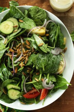 spinach salad w/toasted pepitas and creamy vegan dressing via minimalist baker