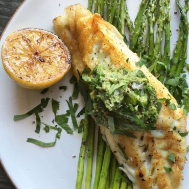 chilean sea bass with spinach avocado pesto served on a bed of asparagus* via delish